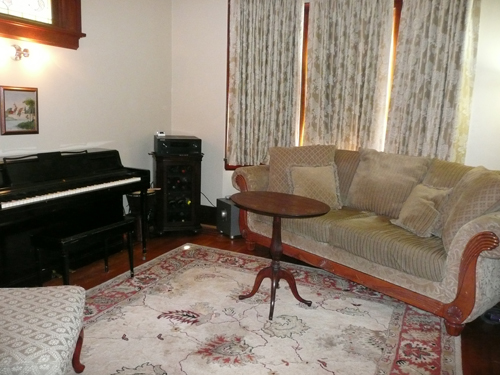 New traditional draperies, piano center stage and sofa on a diagonal with the right color area rug!